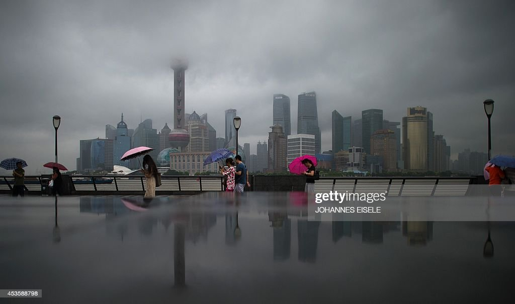 People with umbrellas stand in the rain in front of the skyline of the Lujiazui Financial District in Pudong along the Huangpu River in Shanghai on...