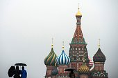 People with umbrellas walk under the rain on Moscow's Red Square on October 15 2014 AFP PHOTO / DMITRY SEREBRYAKOV
