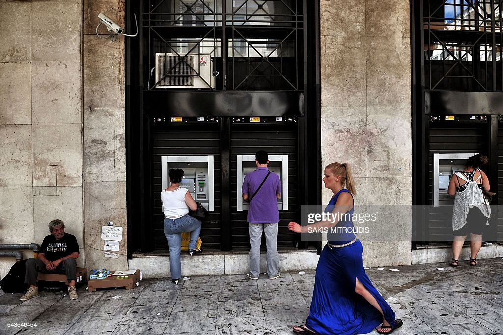 People withdraw money from ATM machines next to a beggar in Thessaloniki on 29 June, 2016. For a year the Greeks had to get used to not being able to withdraw more than 420 euros per week from the bank, a measure decided by credit control in full emergency which contributed to the stagnation of the economy. / AFP / SAKIS