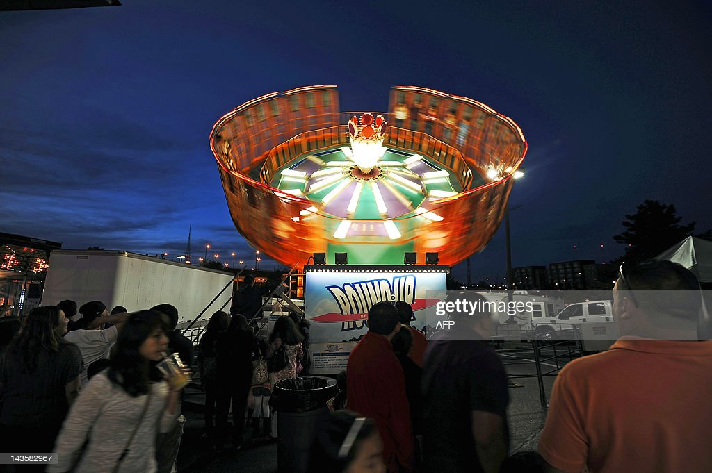 People wonder around rides at a carnival in Wheaton Maryland on April 29 2012 AFP PHOTO/Jewel Samad