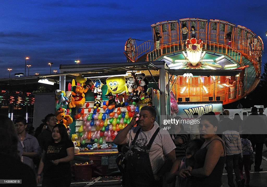 People wonder around various rides and stores at a carnival in Wheaton Maryland on April 29 2012 AFP PHOTO/Jewel Samad