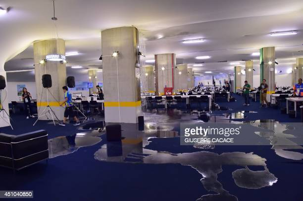 People work after the media center at Estadio das Dunas in Natal was flooded on June 22 2014 during the 2014 FIFA World Cup football tournament in...