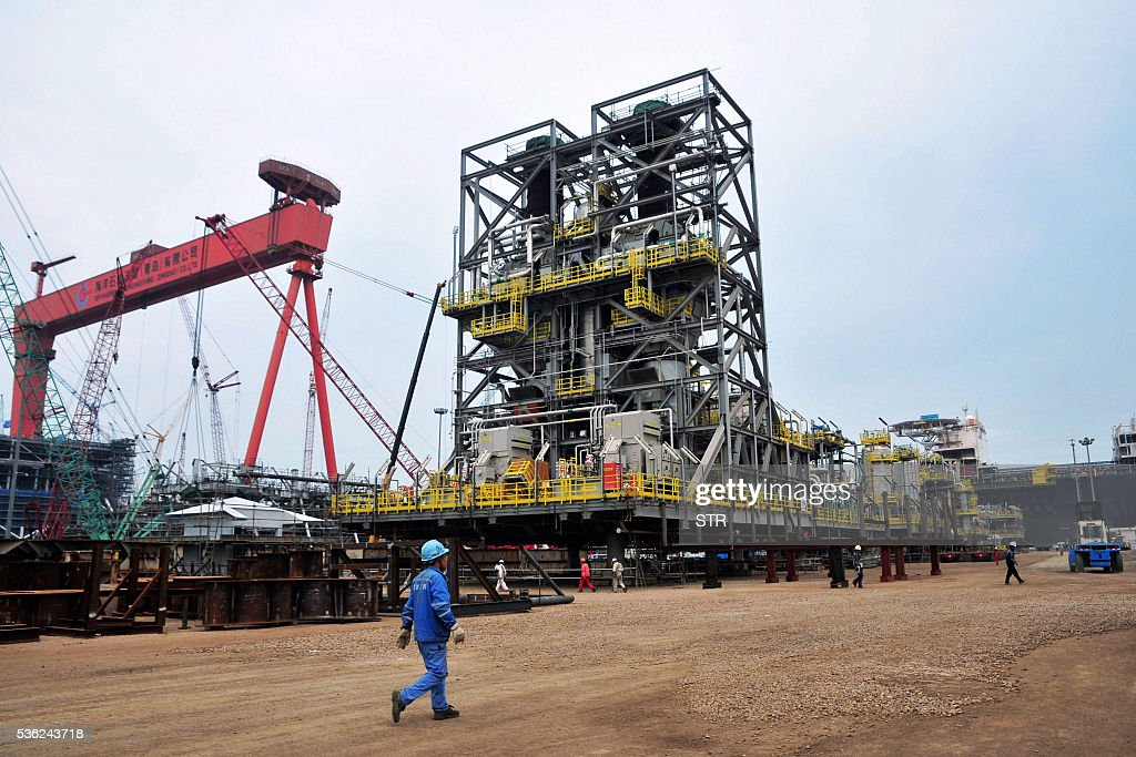 People work at an offshore oil engineering platform in Qingdao, east China's Shandong province on June 1, 2016. Activity in Chinese factories expanded for the third straight month in May, official data showed, a further sign of stabilisation in the world's second largest economy. / AFP / STR / China OUT