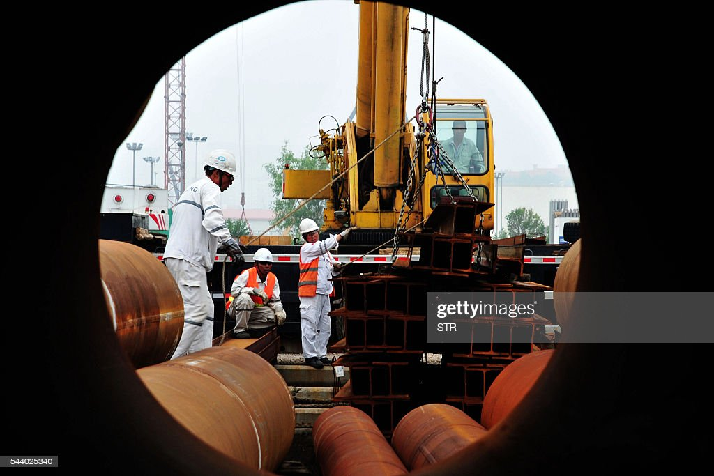 People work at an offshore oil engineering platform in Qingdao, east China's Shandong province on July 1, 2016. Activity in Chinese factories suffered its sharpest deterioration for four months in June, figures showed on July 1, as weak demand and industrial overcapacity weighed on the world's second-largest economy. / AFP / STR