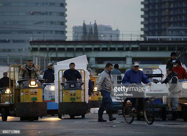 People work at Tokyo's Tsukiji fish market in the early morning of Dec 13 2016 The relocation of the market to the nearby Toyosu area scheduled for...