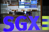 People work in an office at the Singapore Exchange on July 27 2016 Asian markets mostly rose on July 27 as the Federal Reserve prepares to wrap up a...