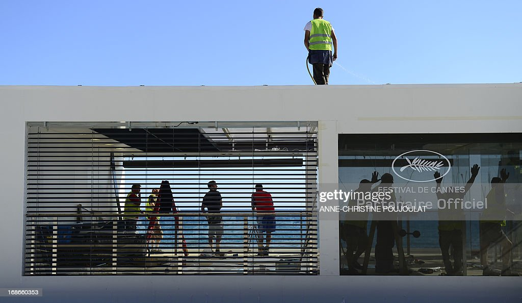 People work in front of a private beach on May 13, 2013 in Cannes, two days before the opening of the 66th Cannes Film Festival.