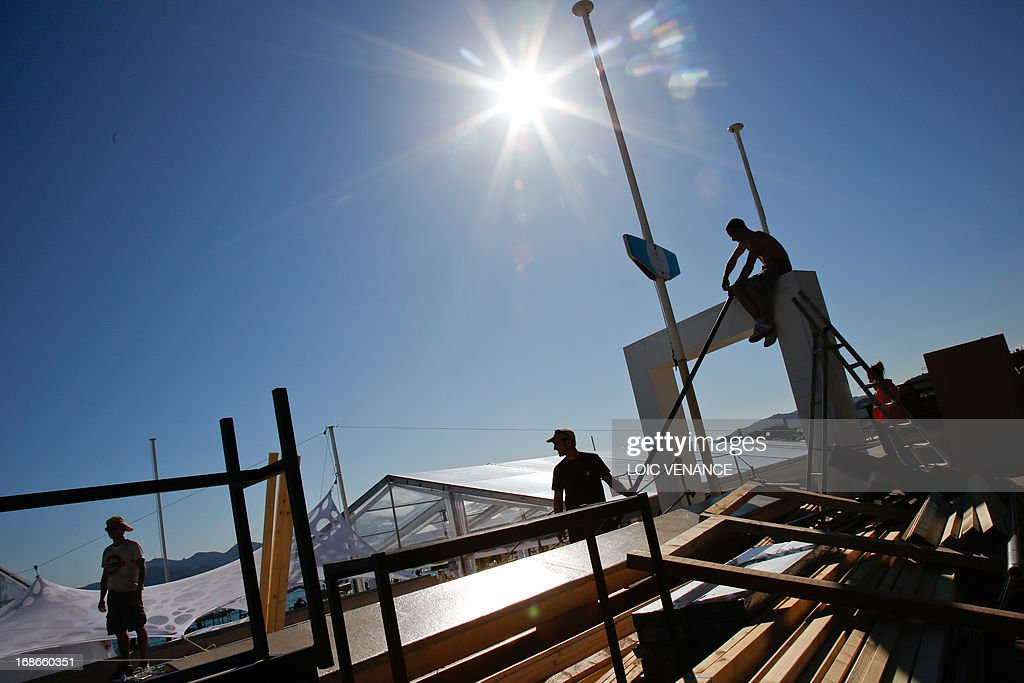 People work in front of the private beach on May 13, 2013 in Cannes, two days before the opening of the 66th Cannes Film Festival.