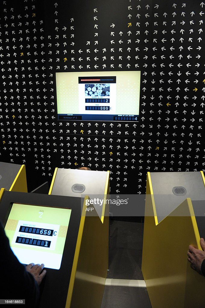 People work on March 25, 2013 on a game explaning the auction system on the eve of the opening of the exhibition 'L'Economie: krach, boom, mue ?' at the Cite des Sciences in Paris. AFP PHOTO ERIC PIERMONT