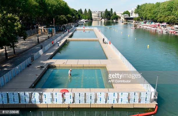 People work to set up three swimming pools in the Bassin de la Villette in Paris on July 7 2017 GUAY