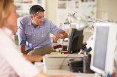 Male Worker Sitting On Desk In Busy Creative Office