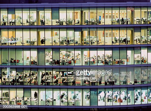People working in glass sided office building, night : Foto de stock