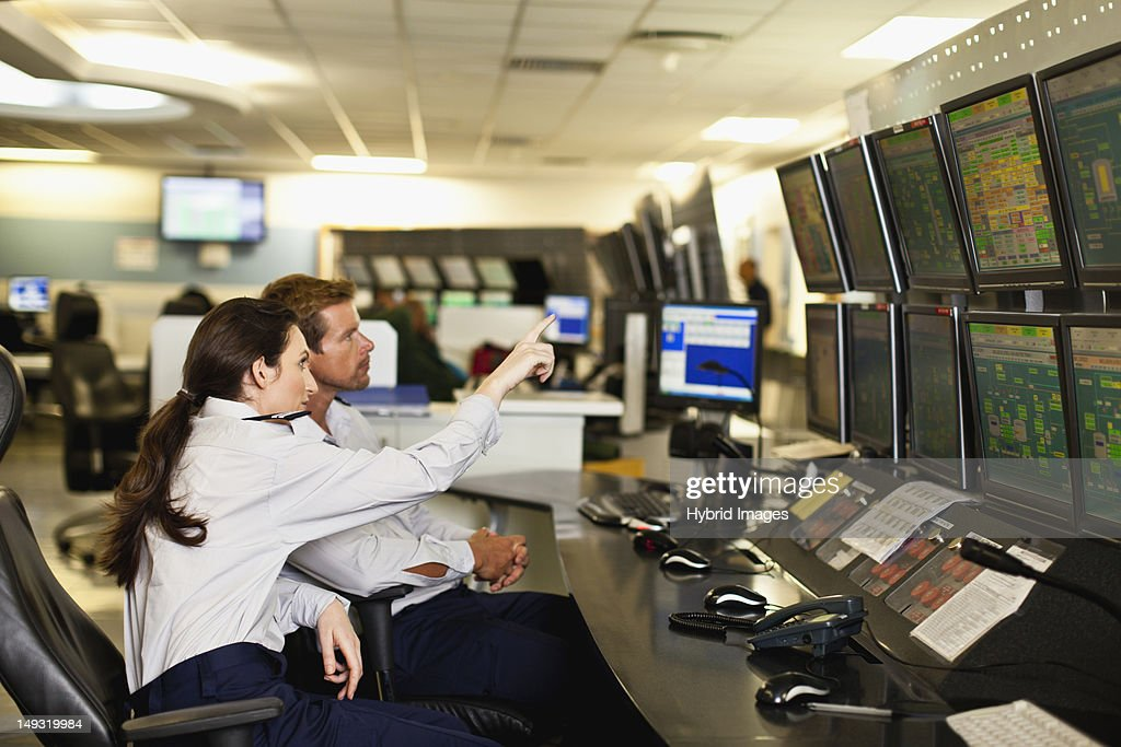 People working in security control room