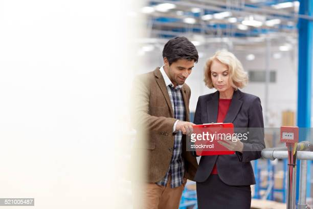 People working inside a factory discussing logistics