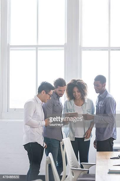 Vier Menschen arbeiten auf einem digitalen tablet im Büro.