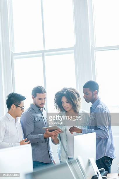 4 people working on a digital tablet in an office.