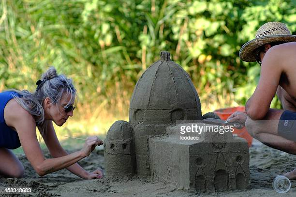 People working on a sand church