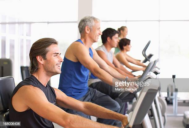 People working out on exercise machines in gymnasium