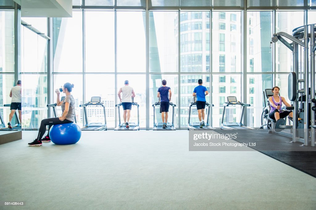 People working out on treadmills in gymnasium