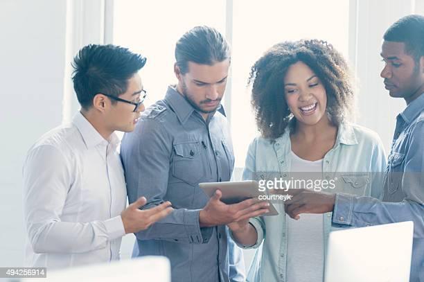 Vier Menschen arbeiten zusammen in einem kleinen Büro.
