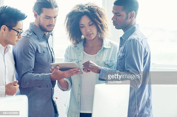 4 people working together in a small business office.