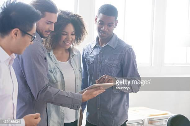 4 Personen gemeinsam arbeiten auf einem digitalen tablet