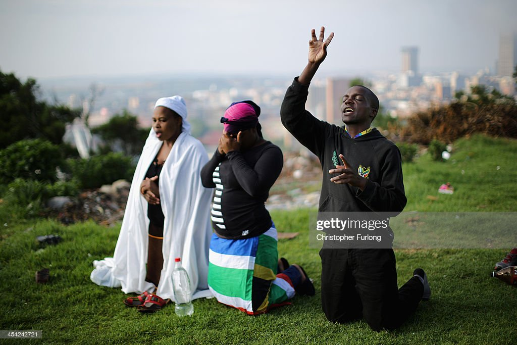 People worship on a hill overlooking Johannesburg as they remember and mourn Nelson Mandela. South Africans are observing a national day of prayer in parks and churches on December 8, 2013 in Johannesburg, South Africa. Mandela, also known as Madiba, passed away on the evening of December 5th, 2013 at his home in Houghton at the age of 95. Mandela became South Africa's first black president in 1994 after spending 27 years in jail for his activism against apartheid in a racially-divided South Africa