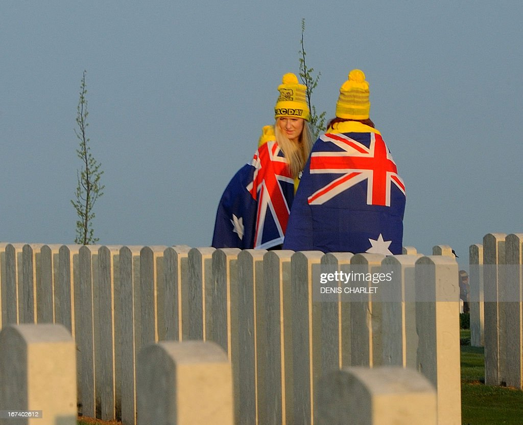 People wrapped in Australian flags walk past graves at the Australian War Memorial in the northern French city of Villers-Bretonneux, on April 25, 2013, as part of the Australian and New Zealand Army Corps (ANZAC) Day ceremony. Anzac Day commemorations are held each year on April 25 to mark the anniversary of the ill-fated landing of the Australian and New Zealand Army Corps (ANZAC) at Gallipoli in World War I.