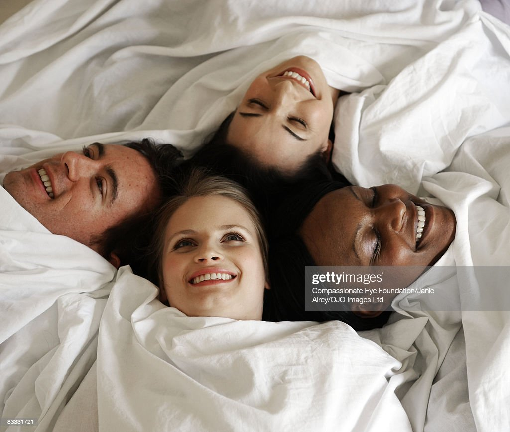 People wrapped in sheet on bed