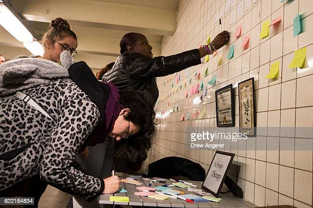 People write and hang postit notes many with politically themed messages on a wall at the 6th Avenue subway station as part of a public art project...
