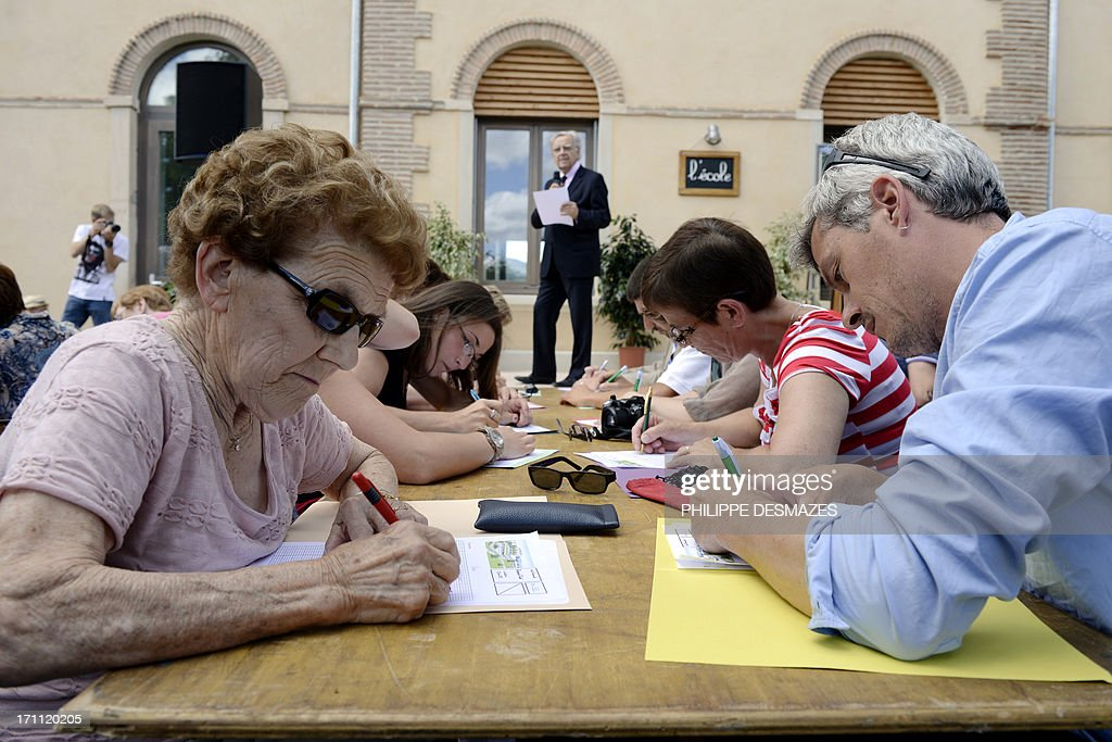 People write as Bernard Pivot (C), former journalist and member of the academie Goncourt, a French literary organization, dictates on June 22, 2013 during the inauguration of the Bernard Pivot school in Vaux-en-Beaujolais, eastern France, the village which inspired the setting for the French satirical novel 'Clochemerle' by Gabriel Chevallier.