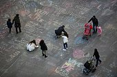TOPSHOT People write messages on the ground at a makeshift memorial at Place de la Bourse following attacks in Brussels on March 22 2016 Airlines...
