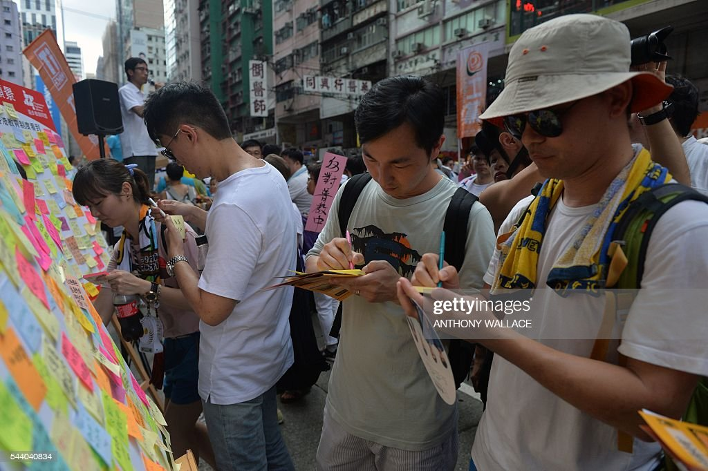 People write notes before sticking them onto a sign board, reminiscent of the Lennon Wall seen during the 2014 pro-democracy protests, during a pro-democracy rally in Hong Kong on July 1, 2016, traditionally a day of protest which also marks the anniversary of the handover from Britain to China in 1997. Protesters took to the streets of Hong Kong on July 1 to mark the anniversary of the city's handover from Britain to China, with pro-independence groups rallying for the first time amid fears Beijing is tightening its grip. / AFP / ANTHONY