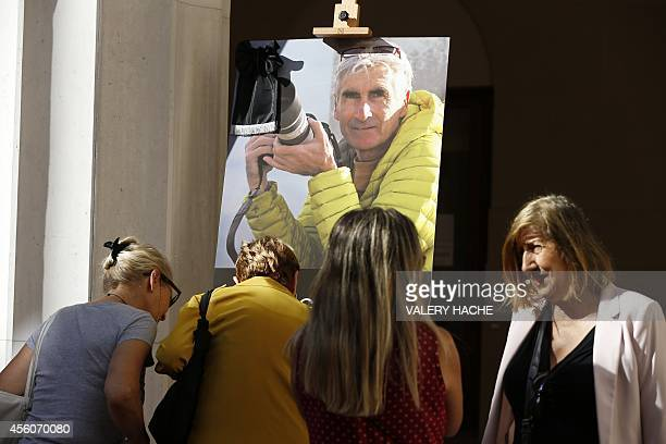 People write notes in tribute to mountainguide Herve Gourdel near to a picture of him set in front of the city hall on September 25 in Nice...