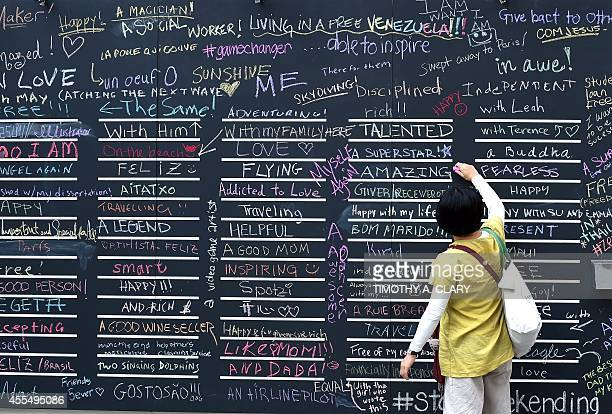 People write on a chalkboard with the title ' I Want to Be' at a public art display in Madison Square Park in New York September 15 2014The project...