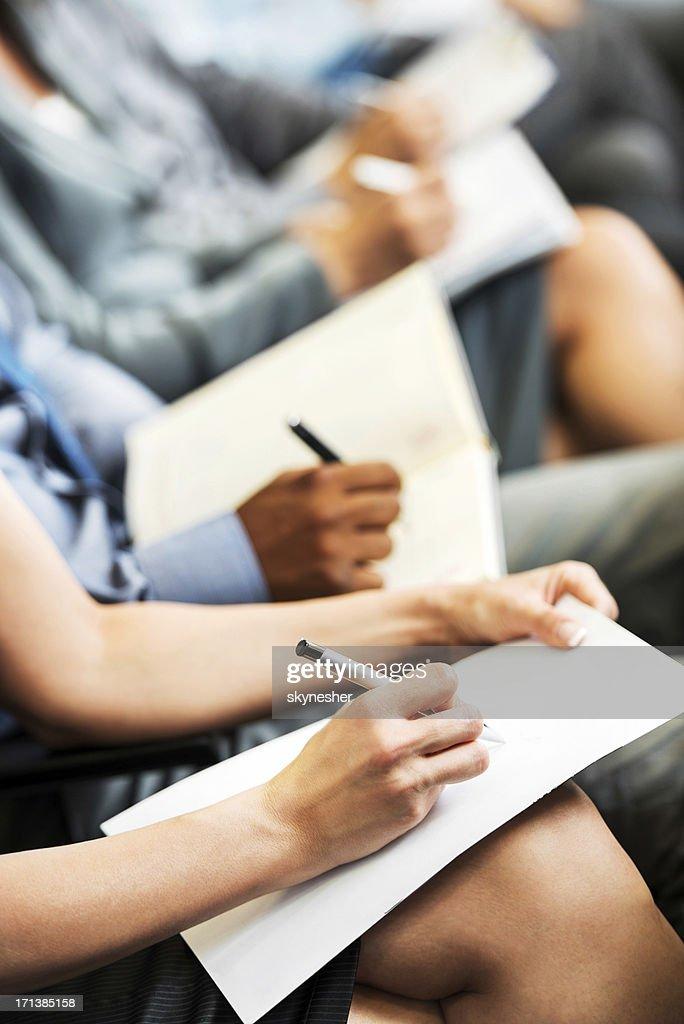 People writing on a seminar.