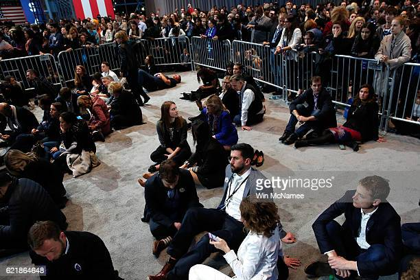 People wsit on the floor as they watch the voting results at Democratic presidential nominee former Secretary of State Hillary Clinton's election...