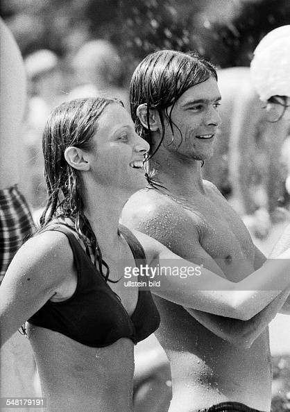 people young couple in an openair swimming pool bikini bathing trunks fun aged 18 to 25 years