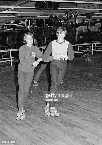 people young couple on rollerblades in a sports hall trousers pulli aged 15 to 18 years