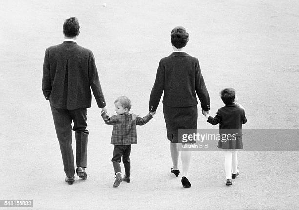 people young family takes a walk all go hand in hand man aged 25 to 35 years woman aged 25 to 35 years boy aged 3 to 4 years girl aged 5 to 7 years