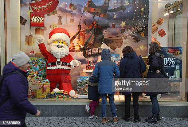 Peoplelook at a Christmasthemed shop window displaying a Santa Claus made of Legos on December 4 2016 in Berlin Germany Christmas season is in full...
