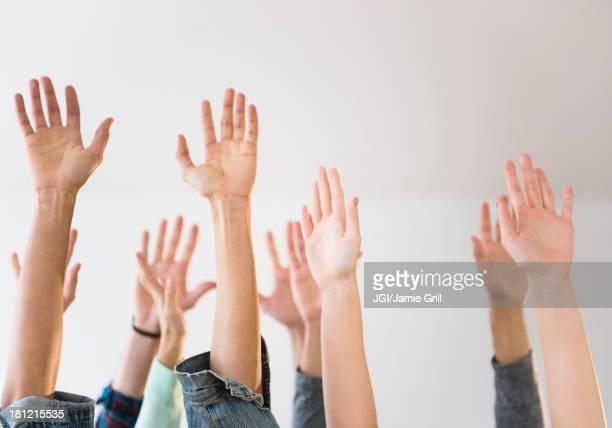 People's hands raised in air