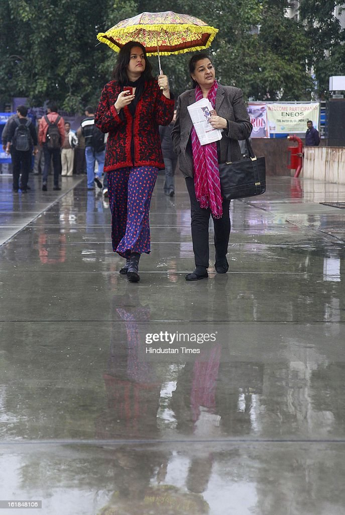 Peoples use colour full umbrella to cover rain in the capital on February 17, 2013 in New Delhi, India. The chilly weather in North India continues as rains lash several areas in Delhi, Uttarakhand, Himachal Pradesh and Uttar Pradesh.
