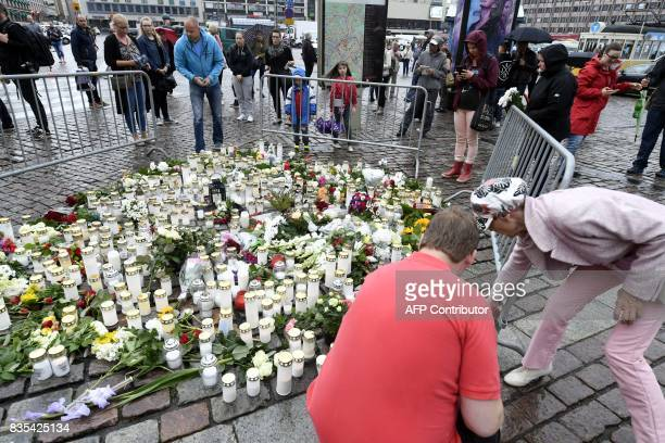 Peopole lay candles and flowers at the makeshift memorial for the victims of Friday's stabbings at the Turku Market Square Finland on August 19 2017...
