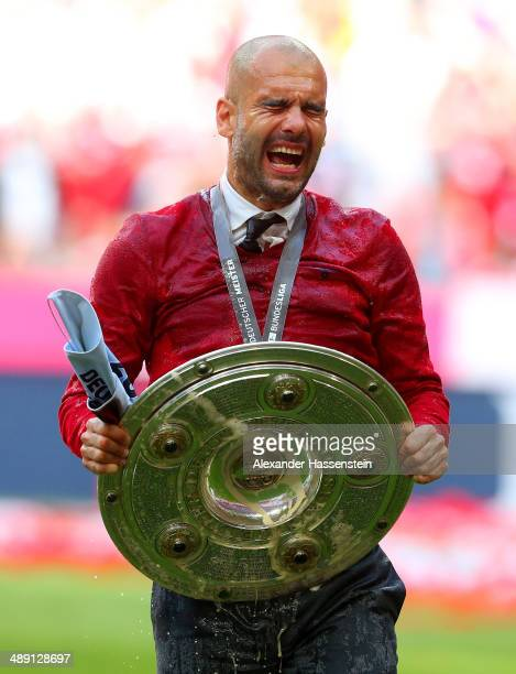 Pep Guardiola head coach of Bayern Muenchen celebrates with the Bundesliga championship trophy as he is soaked after the Bundesliga match between...
