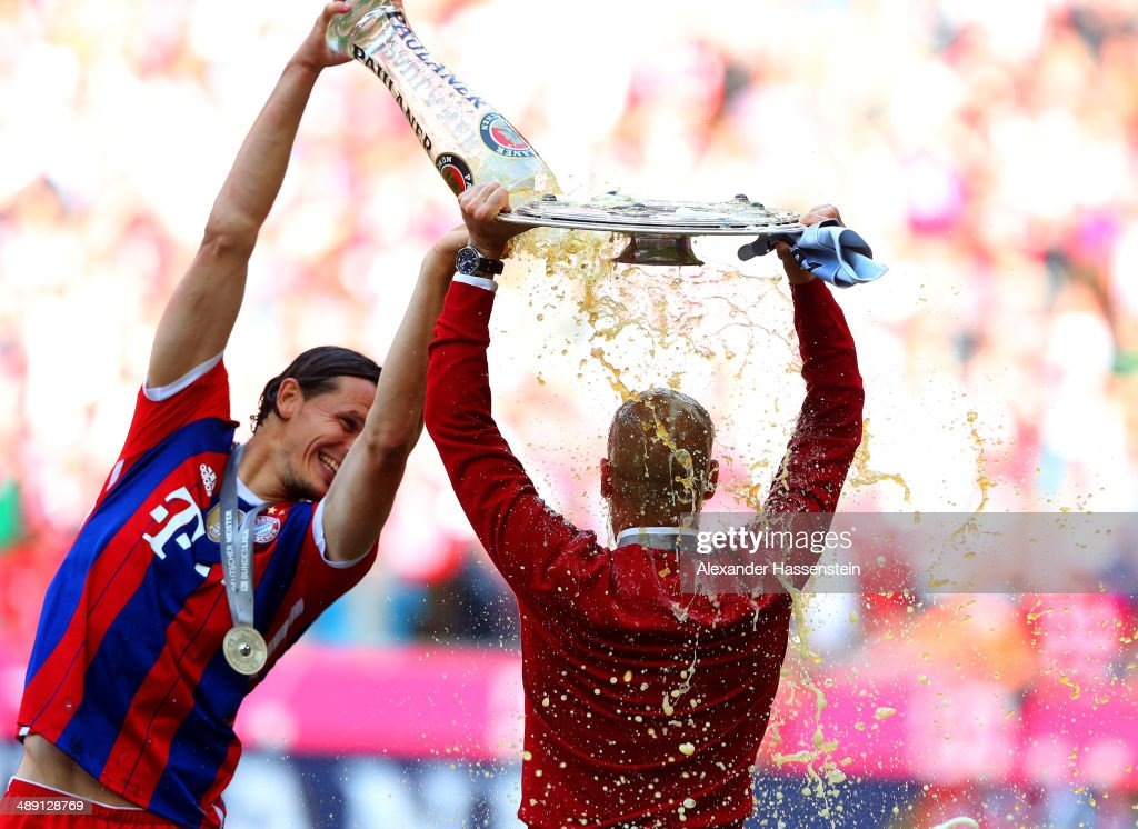 Pep Guardiola head coach of Bayern Muenchen is showered with beer by Daniel Van Buyten as he celebrates with the Bundesliga championship trophy after the Bundesliga match between Bayern Muenchen and VfB Stuttgart at Allianz Arena on May 10, 2014 in Munich, Germany.