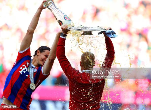 Pep Guardiola head coach of Bayern Muenchen is showered with beer by Daniel Van Buyten as he celebrates with the Bundesliga championship trophy after...