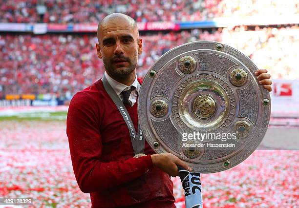 Pep Guardiola head coach of Bayern Muenchen poses with the Bundesliga championship trophy in celebration after the Bundesliga match between Bayern...