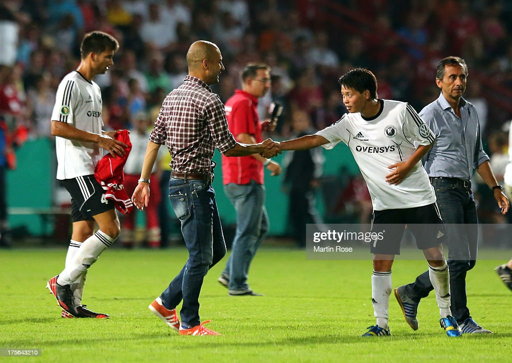 Pep Guardiola (L), head coach of Muenchen shakes hand with Taiki Hirooka of Rehden after the DFB Cup first round match between BSV SW Rehden and Bayern Muenchen at osnatel Arena on August 5, 2013 in Osnabrueck, Germany.