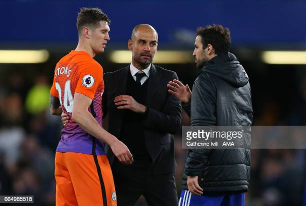 Pep Guardiola manager of Manchester City with John Stones of Manchester City and Cesc Fabregas of Chelsea during the Premier League match between...